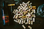 Assortment of Corks next to Wine Bottle, Wineglasses and Corkscrew