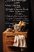 Dishes of nuts and breadsticks surrounded by cork bark on chest of drawers in front of menu on blackboard