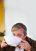 Man looking at the camera while the lower part of his face is covered as he drinks from a white soup bowl