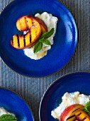 Grilled peaches on burrata drizzled with honey and garnished with mint leaves on cobalt blue plates