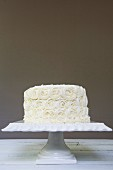 A white wedding cake frosted with roses