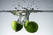 Limes falling into water
