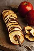Getrocknete Apfelringe und frische Äpfel auf Holzbrett