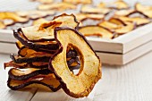 A stack of dried apple rings in front of a drying rack