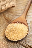 Unrefined cane sugar on a wooden spoon