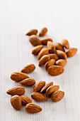 Whole almonds on a white wooden surface