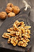 Walnuts on a wooden board next to whole walnuts in their shells