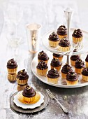 Mud cakes topped with ganache in praline cases on a cake stand