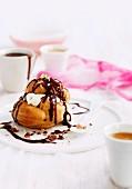 Profiterole mit Sahnecreme, Schokoladensauce und Mandeln