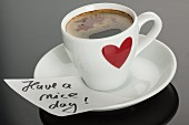 An espresso in a cup with a red heart