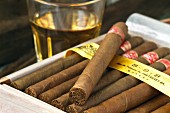 A box of Cuban cigars in front of a glass of rum