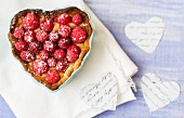 A raspberry tart in a heart-shaped baking tin