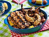 Grilled prawn kebabs and lobster tails on a bed of corn cobs and red potatoes