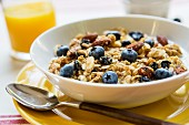 Muesli with fresh blueberries and a glass of orange juice