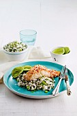 A fillet of fish with a coconut crust on a bed of herb rice