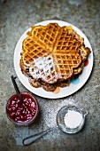 Waffles with icing sugar and strawberry jam