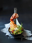 Prawns with vegetables and chives on a spoon