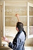 A man reaching for wine glasses in a wall cupboard