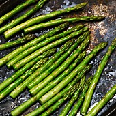 Green asparagus drizzled with olive oil on a baking tray
