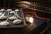 Freshly baked biscuits on sticks in front of an oven