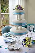 Dreistöckige blau-weisse Hochzeitstorte mit Blumendeko auf gedecktem Tisch