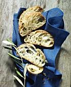 Einige Scheiben Oliven-Ciabatta auf Tuch mit Olivenzweig