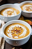 Cream of pumpkin soup garnished with sour cream and pecan nuts