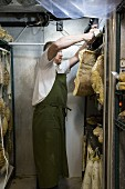 A butcher hanging sides of bacon in a refrigerated room