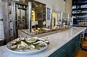 A fish restaurant with a marble bar and a display case with a tray of fresh mussels on the bar