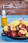 Rustic stew with potatoes, corn cobs, sausage and prawns