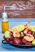 Rustikaler Eintopf mit Kartoffeln, Maiskolben, Wurst und Garnelen