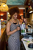 A young woman with a mixer making a smoothie