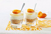 Mini cheesecakes in glasses garnished with apricots