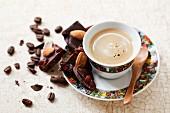 Eine Tasse Espresso und Schokolade mit Trockenfrüchten und Mandeln