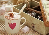 Hot chocolate with marshmallows and dripping cream in a mug with a pink heart
