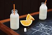 Mini bottles of milk and orange segments on a chalk board