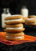 Pumpkin and ginger whoopie pies stacked on an orange napkin and dusted with icing sugar (USA)