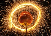 A toffee apple on a twig in a light circle created with a sparkler