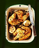 Garlic chicken with thyme in a roasting dish (seen from above)