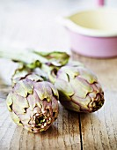 Two artichokes on a wooden surface