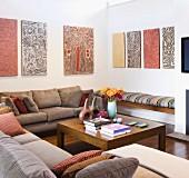 Kunst der Aborigines über Sitzecke mit gemütlichen Sofas und schlichtem Couchtisch aus Edelholz