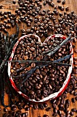 Coffee beans with vanilla pods in a ceramic heart