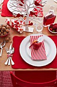 Red and white Christmas place setting with miniature tree ornament