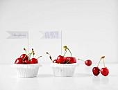 Rote Kirschen in Papierförmchen mit Fähnchen und Sinnsprüchen