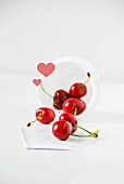 Red cherries falling out of a paper case with hearts