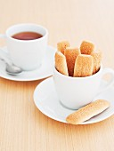 Sponge finger biscuits in a white cup and a cup of tea in the background
