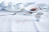 Benutztes weißes Kaffeegeschirr mit bunten Zuckerstreuseln auf weißer Tischdecke