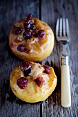 Two baked apples with cranberries on a wooden table with a fork