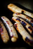 Charred Nuremberg sausages in a pan (close-up)