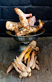 Fresh galangal roots in a bowl with fingerroots on a wooden board